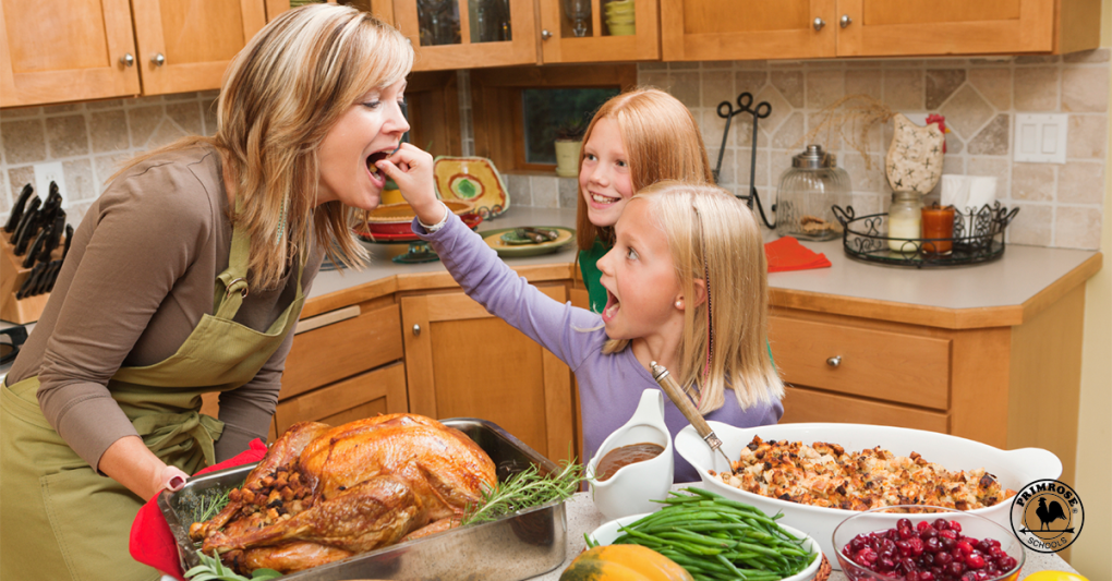 Little girl excitedly offers her mother a bite of their thanksgiving meal as her older sister looks on