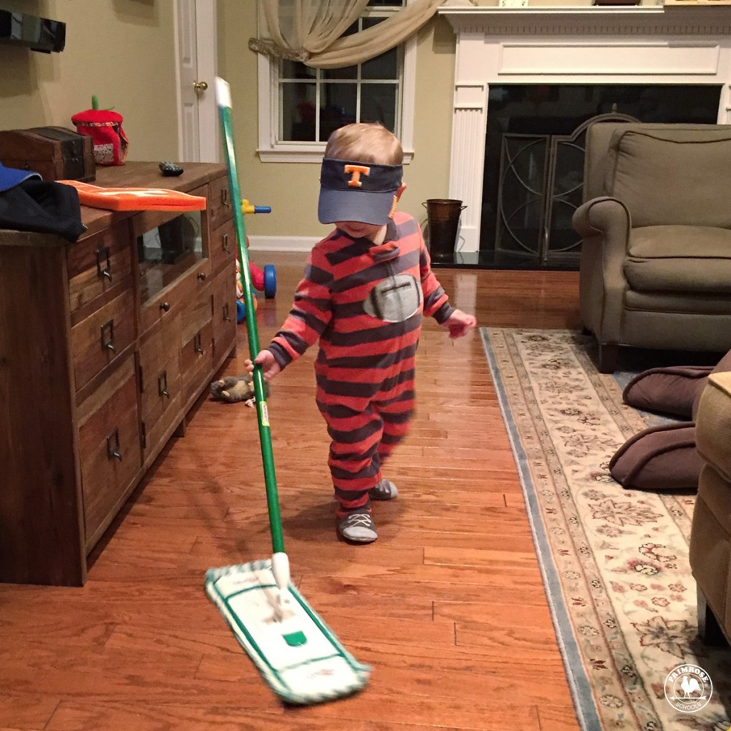 Toddler playing with mop