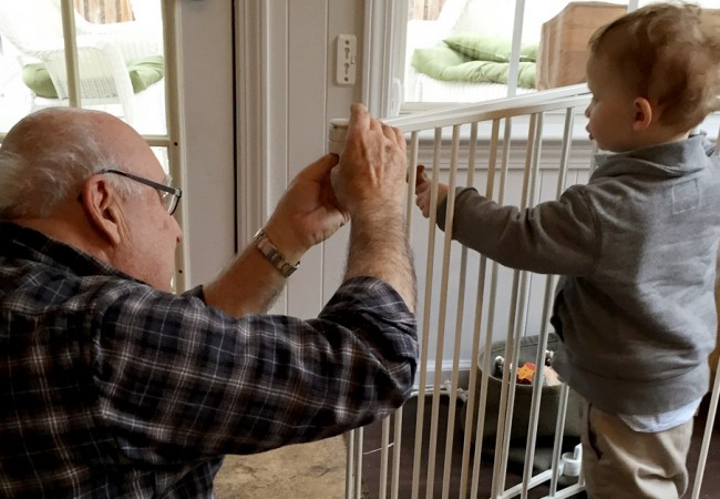 Little boy helps his grandfather assemble a crib
