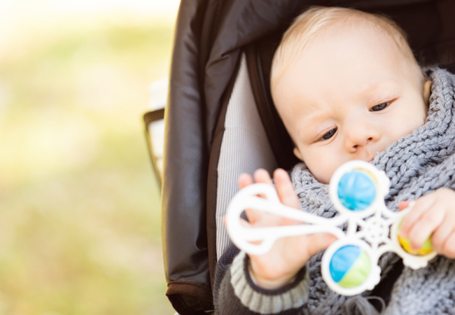 Little baby boy plays with his shaker toy in his pram