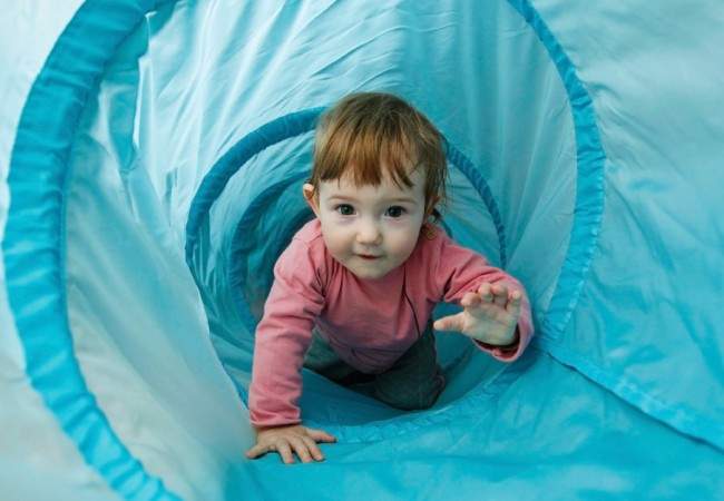 Little girl playing in a tunnel tube, crawling through it and having fun