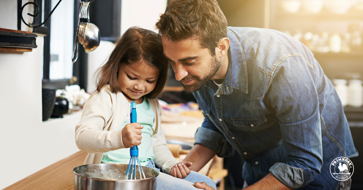 Father helping his young daughter in cooking