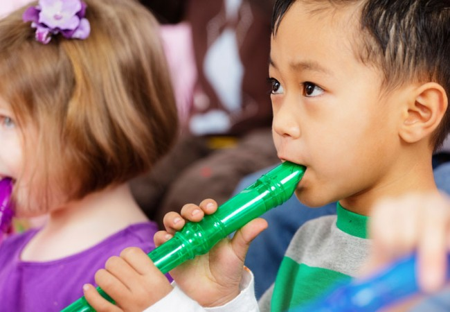 A young boy and girl learn how to play the flute