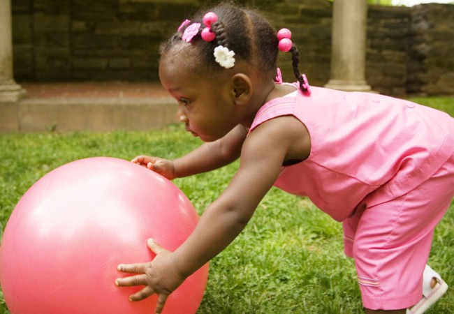 Little girl plays with a balance ball