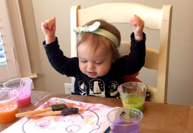 Young girl enjoys water color painting in the kitchen