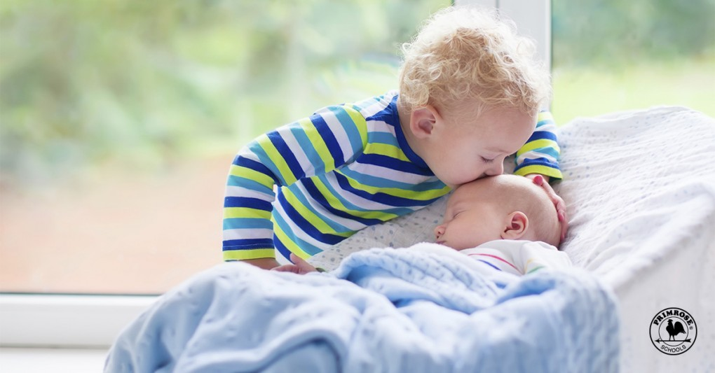 A little boy kisses his newborn baby brother