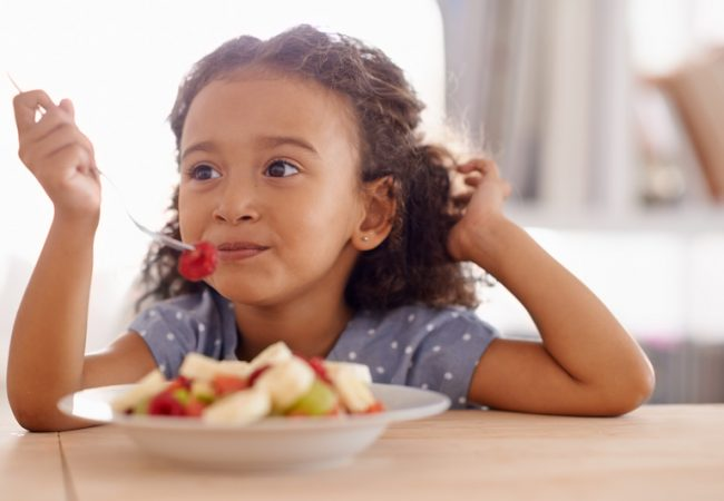 Little girl eats fruit off of fork