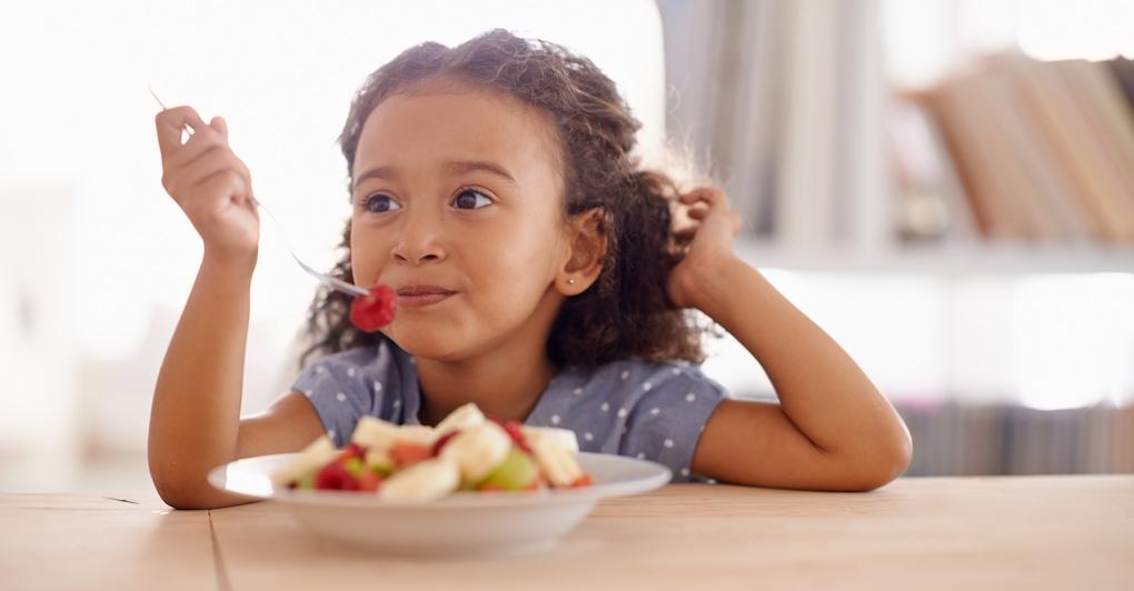 Little girl eats fruit off of fork
