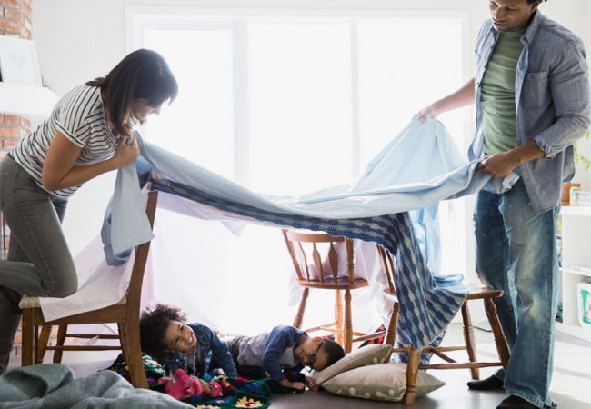 Parents build a blanket fort for their children as they smile happily sitting under it