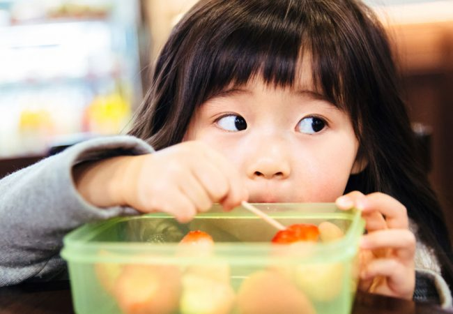 A picky young girl looks away from her bowl of fruit