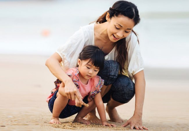 Mother and daughter happily make patterns in the sand at the beach