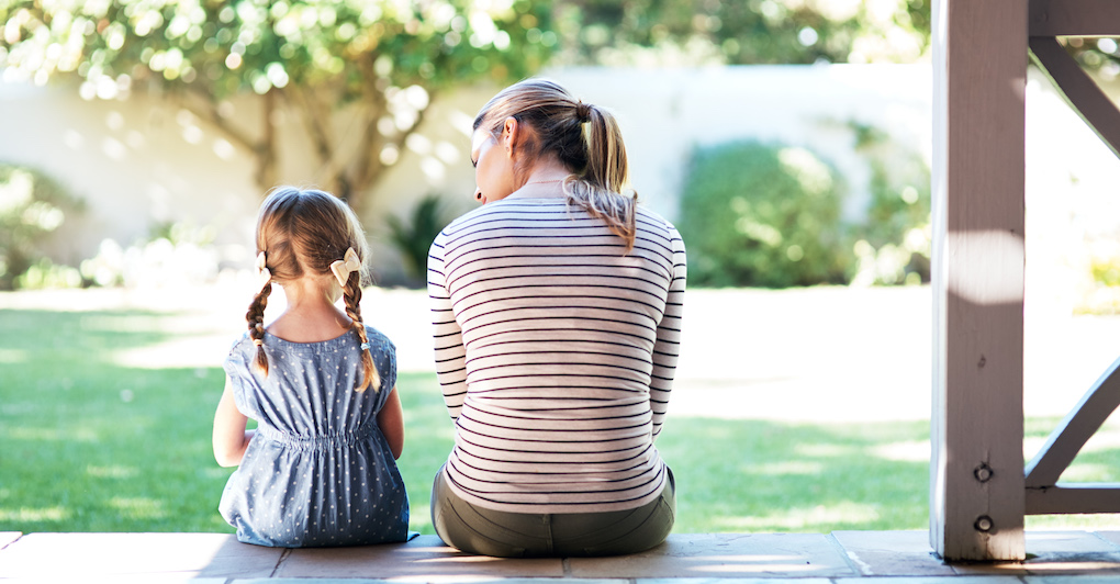 Woman and daughter sit on porch in backyard and have discussion
