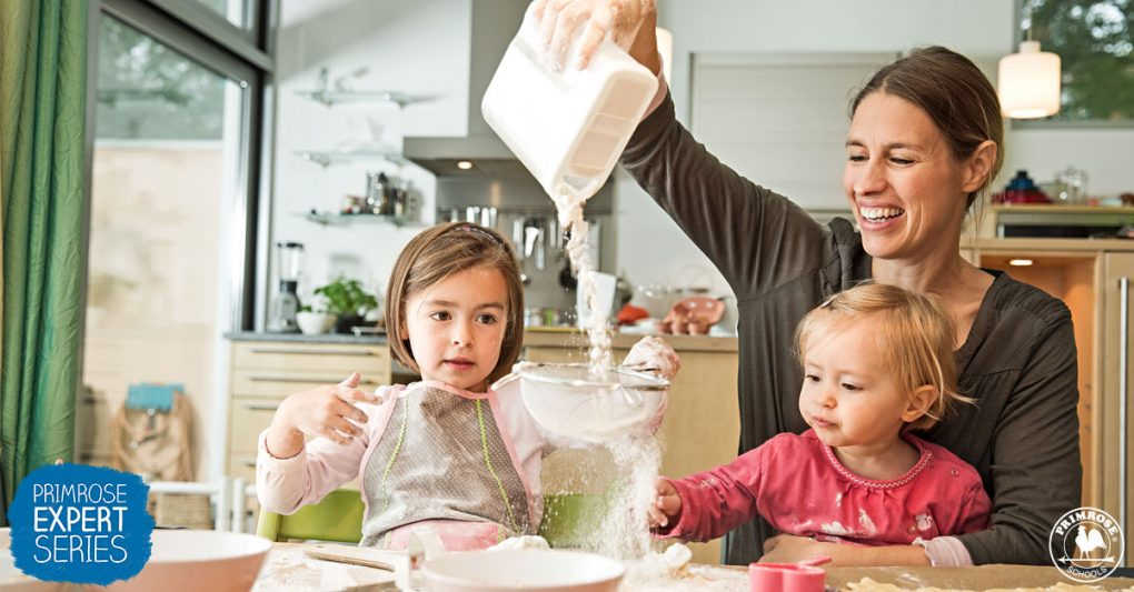 Little girl holds a sieve as her mother pours flour through it