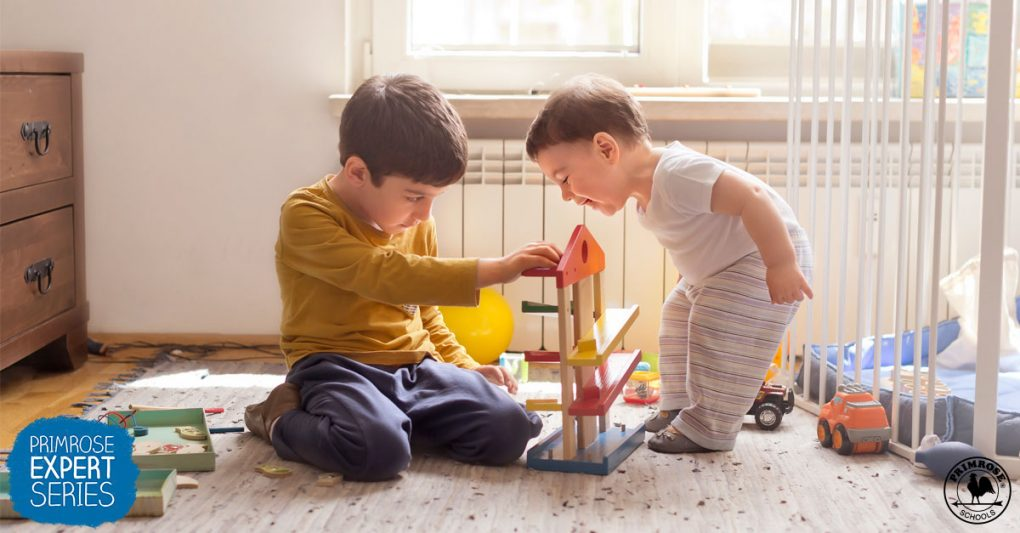 Little boy plays with blocks as his baby brother curiously observes him