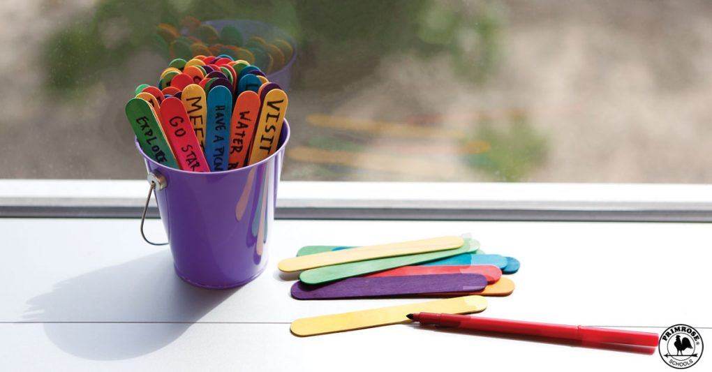 Colored popsicle sticks with summer plans written on them