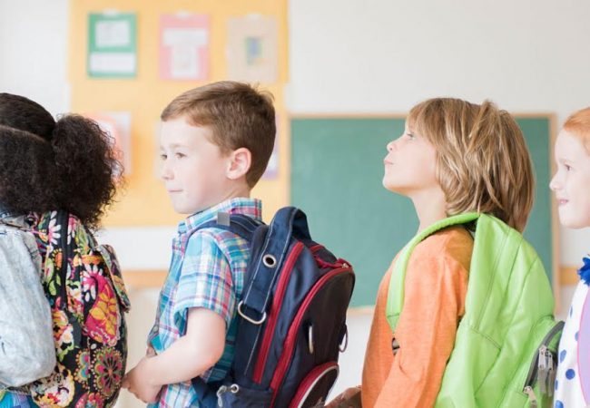 Excited students line up with colorful backpacks on their first day of school