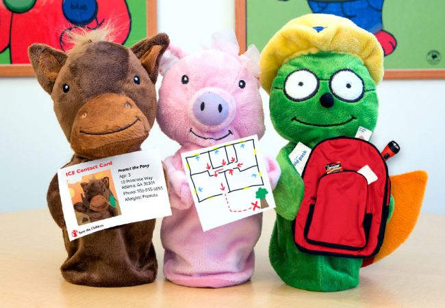 Primrose puppets hold an ICE contact card, emergency maze game and an emergency supplies backpack