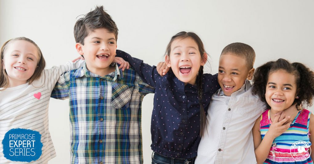 A diverse group of young children holding each other smiling