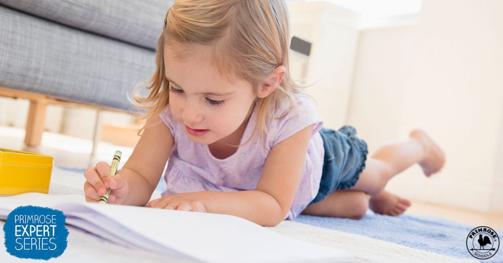 A little girl coloring in her living room