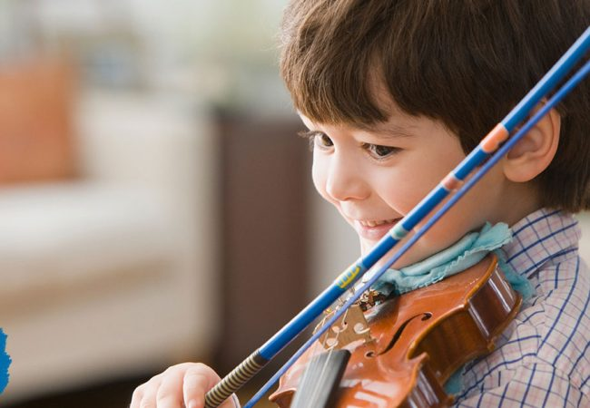 Little boy happily plays a violin