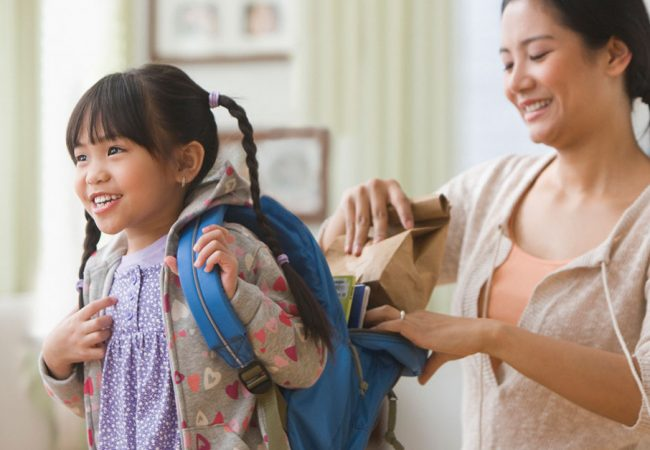Mother packs her daughter's lunch as she prepares to leave for school