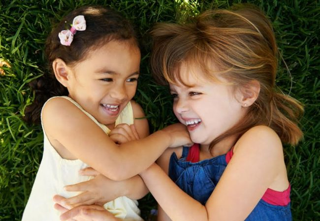 Two little girls tickling each other playfully while lying in the grass