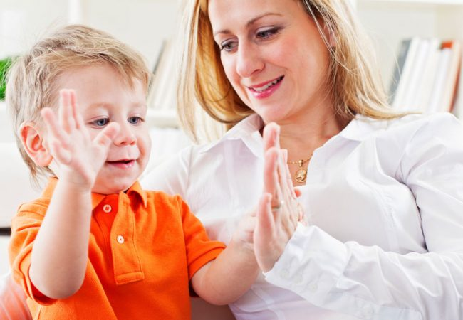 Mother teaching her young son sign language