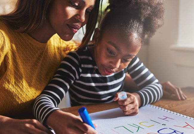 Preschooler practices writing alphabet at home with help from mom