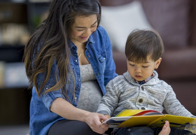 Pregnant mother sits and reads a book with her toddler son