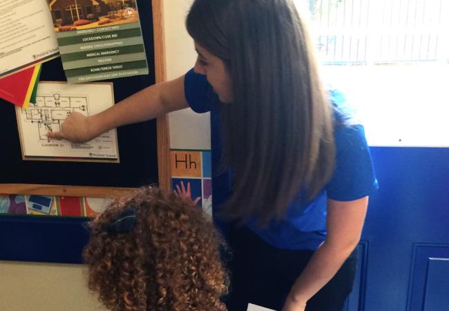 A Primrose teacher points out exit routes on a school map