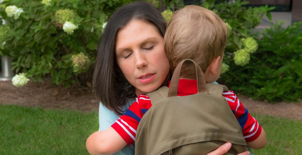 Working Mom looking sad and guilty hugging her preschooler