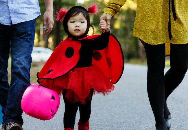 Little girl dressed as a ladybug going trick-or-treating with her parents