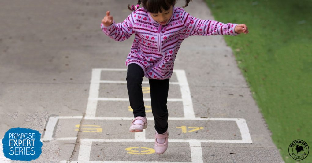 A little girl playing hopscotch on the sidewalk