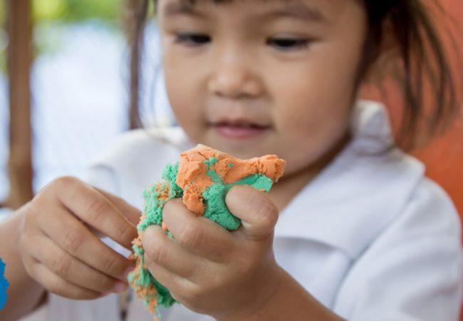 A little girl fiddles with playdough