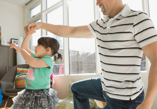 Father twirling his daughter while dancing