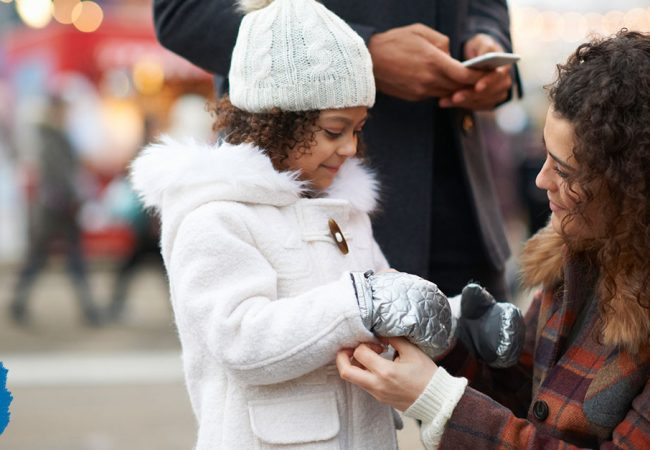Mother ensuring her daughter's gloves and coat are snug