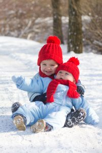 Sibling toddlers playing on snow