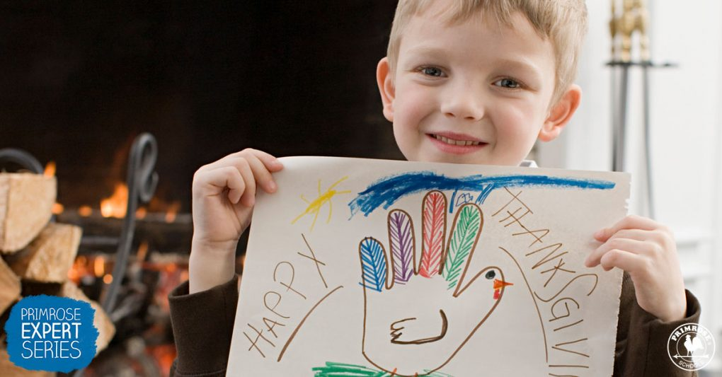 A young boy holds up a drawing of a hand-shaped turkey with happy thanksgiving written around it