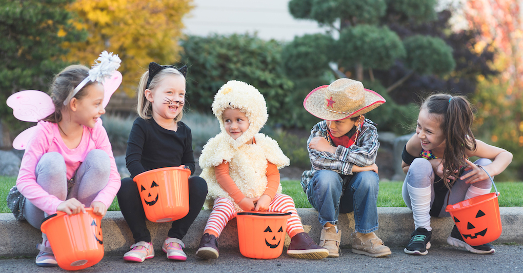 Toddlers in simple Halloween costumes sitting outside