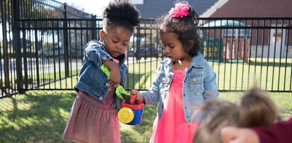 Two Primrose students help each other while playing together in garden