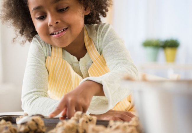A young girl excitedly looks at cookie dough waiting to be bake