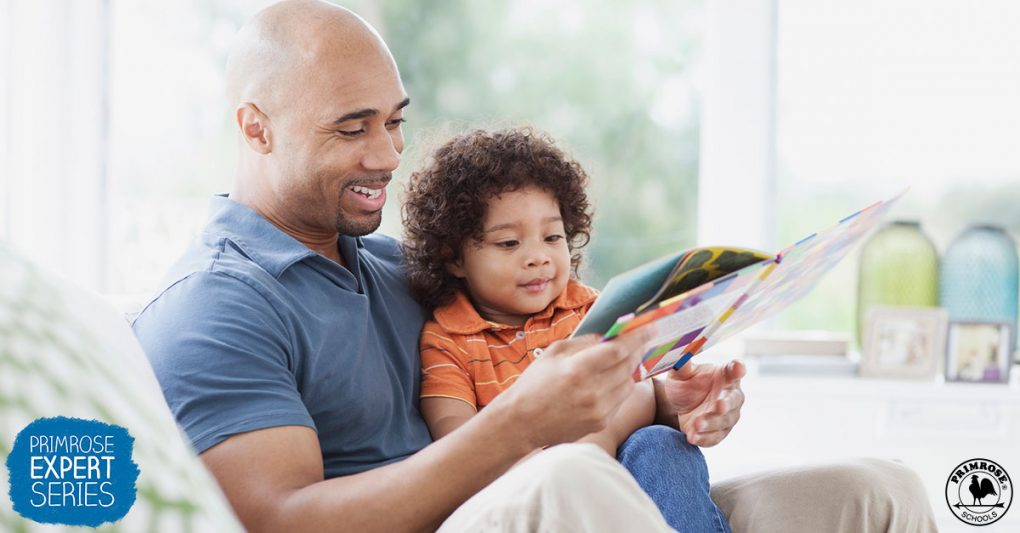 Father happily reads a story book to his young son