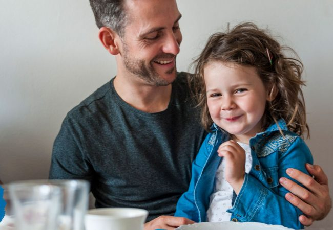 Little girl smiles shyly while her dad looks lovingly at her
