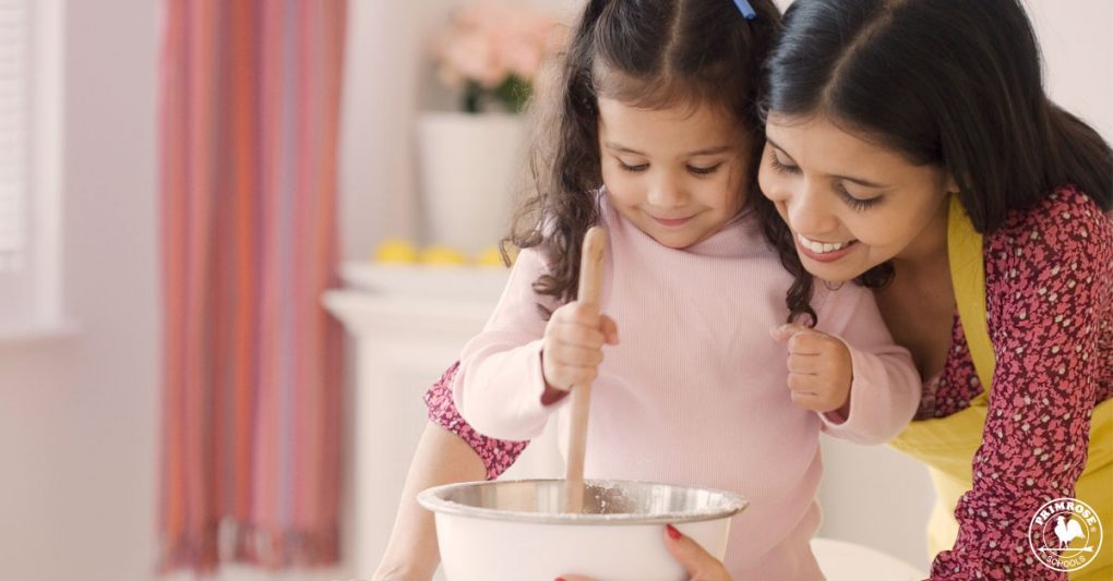 Little girl helps her mother in mixing ingredients for a thanksgiving dish