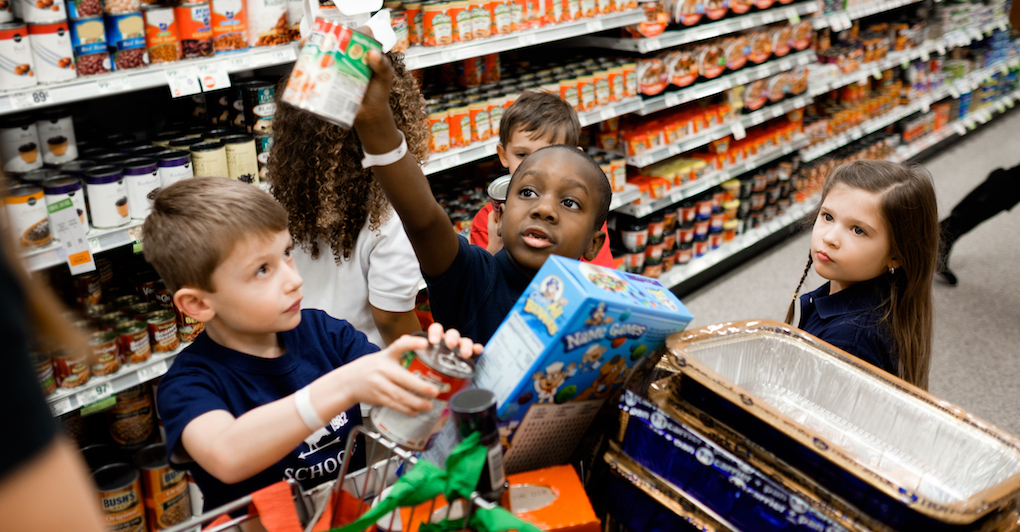 Young kids and preschoolers shop at grocery store to buy food for families in need for a fundraiser