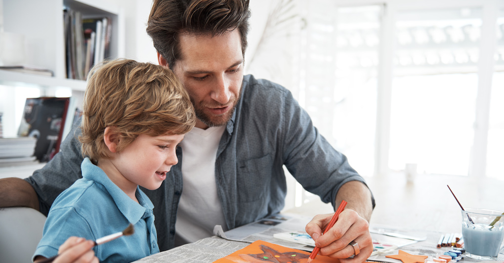 Father and son sit at table and create a holiday craft together.