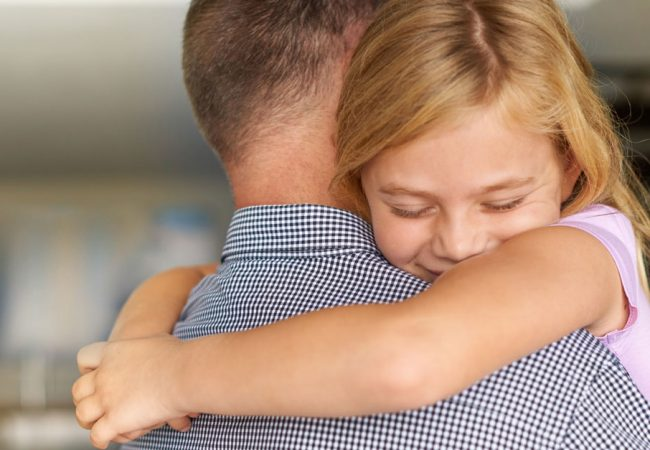 A young happily hugs her father