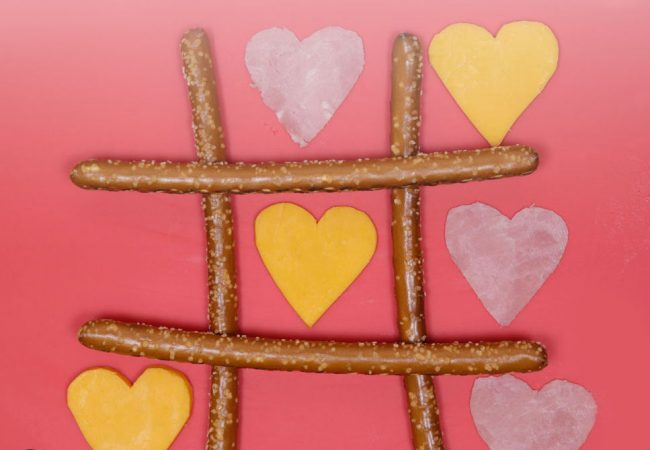 TicTacToe board made from pretzel sticks, ham and cheese heart-shaped cutouts