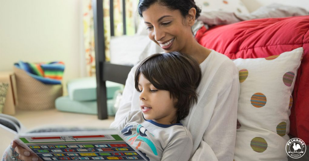 A happy mother looks on as her young son reads a story book