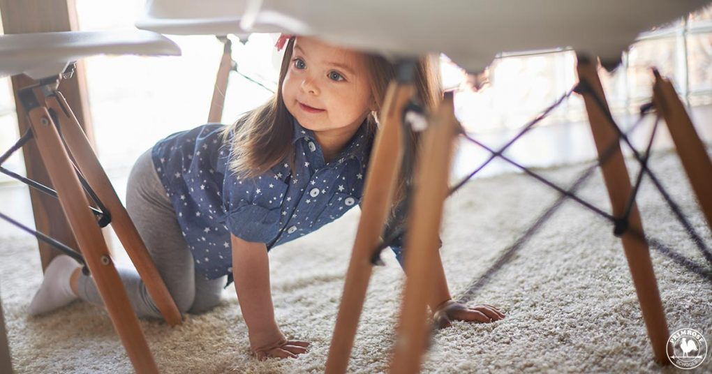 A young girl playing hide and go seek under the table
